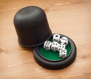 Dices with cup. On the wooden table Royalty Free Stock Photo