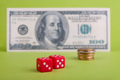 Dices with dollar and coins. Two  dices in front of dollar  banknote and coins Stock Photo