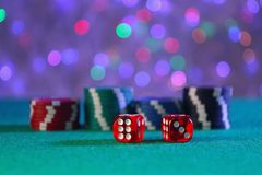 Dices and gambling chips on green table stock photo