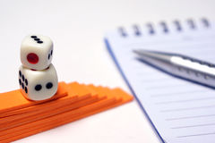 Dices with pen and notepad Royalty Free Stock Photography