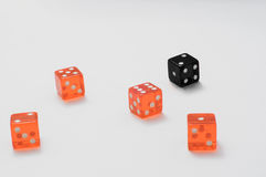 Dices. Playing black dice  and orange dices on the table Stock Photos