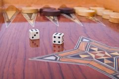 Dices with reflection on wooden backgammon board. Wooden handmade backgammon board with chips and two dices on white background Royalty Free Stock Photo