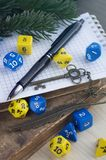 Dices for rpg, dnd, tabletop, or board games, pen, notebook, old decorated key, old books on a wooden surface. stock image