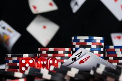 Dices and two ace cards surrounded by poker chips background of falling cards royalty free stock photography