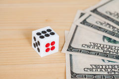 Dices on wood table with  dollar Stock Photos