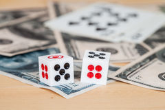 Dices on wood table with US dollar and card Royalty Free Stock Image