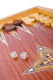 Dices on wooden handmade backgammon board isolated. Wooden handmade backgammon board with chips and two dices on white background Stock Images