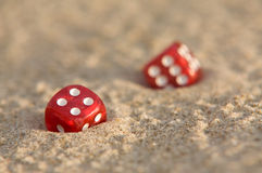 Dicespair. A pair of red dices in sand Royalty Free Stock Photos
