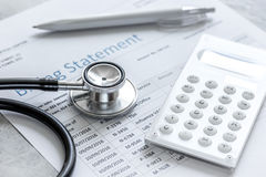 Dichiarazione treatmant medica di fatturazione con lo stetoscopio ed il calcolatore su fondo di pietra Fotografia Stock Libera da Diritti