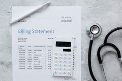 Dichiarazione treatmant medica di fatturazione con lo stetoscopio ed il calcolatore sulla vista superiore del fondo di pietra Immagine Stock