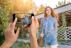 Dicht beeld die van vrouwelijke handen mobiele telefoon met de wijze van de fotocamera op het scherm houden Bebouwd beeld van por stock afbeelding