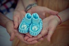 Dicht beeld met zachte nadruk op weinig hand van het babykind - de gemaakte wolschoenen houden door moeder en vaderhanden dromend stock foto's