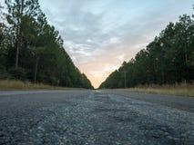 Dicht bij zonsondergang langs een eenzame landelijke weg stock foto