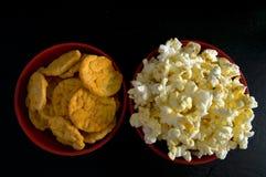 Dicht Hoogste Weergeven van Beboterde Popcorn en BBQ Rijstspaanders in Rode Kommen die op Zwarte worden geïsoleerd royalty-vrije stock fotografie
