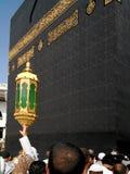 Dicht kader voor Heilige Kaaba in Mekka met mensenhand en lantaarn stock afbeeldingen