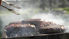 Dicht omhoog draaiend smakelijke koteletten bij grill stock footage
