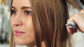Dicht opgedoken van een schitterende jonge vrouw die haar die haar krijgen bij de salon wordt gestileerd royalty-vrije stock foto