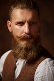 Dicht portret van de gebaarde mens in overhemd en bruin vest royalty-vrije stock foto