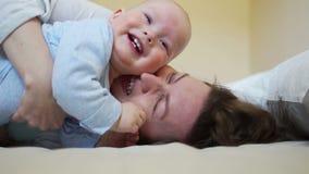 Dicht portret van een baby in de wapens van zijn moeder in de slaapkamer in het ochtendbed stock video