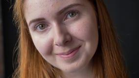 Dicht portret van gezicht die van de gember het jonge vrouw bij camera glimlachen die, vrolijk en gelukkig, op zwarte studioachte stock videobeelden
