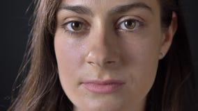 Dicht portret van jonge ernstige mooie vrouw die camera bekijken die, op zwarte achtergrond wordt geïsoleerd stock video