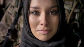 Dicht portret van jonge moslimvrouw in hijab die en camera, bewapende militair met wapen schreeuwen bekijken die zich erachter be stock videobeelden