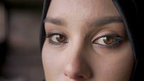 Dicht portret van jonge moslimvrouwen` s ogen die camera in hijab, droevige en gedeprimeerde uitdrukking bekijken