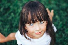 Dicht portret van zeer mooi meisje met een klap, een donker haar en blauwe ogen Royalty-vrije Stock Foto's