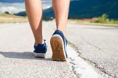 Dicht van de achterkantmening omhoog geschoten van voeten met loopschoenen op de weg royalty-vrije stock foto's