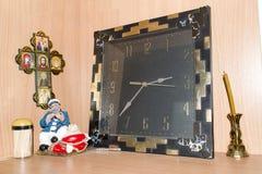 Dichtbij de oude uren een kaars en een pictogram Royalty-vrije Stock Afbeeldingen