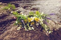 Dichtbij de rivier ligt de bank op een grote rots een kroon van bloemen Stock Foto