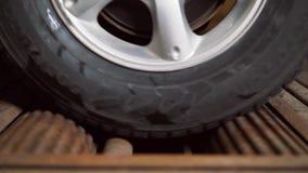 Dichtbij het roterende wiel van de auto aan de tribune voor diagnostiek en machtsmeting van de auto stock video