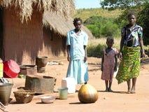 Dichtbij Pweto, Katanga, Democratische Republiek de Kongo: Moeder en dochters die voor hun hut stellen stock afbeelding
