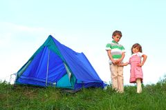 Dichtbij tent, houdt de jongen meisje door hand Royalty-vrije Stock Foto's