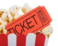 Dichte die omhooggaand van het filmkaartje in een doos popcorn op wit wordt geïsoleerd Stock Foto's