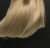 Dichte, gerade blonde Perücke, die auf schwarzem Hintergrund liegt Stockbilder