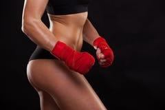 Dichte mening van het atletische meisje stellen in rode verbanden, op de donkere in dozen doende vechter als achtergrond kickbox Royalty-vrije Stock Foto's