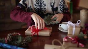 Dichte mening van man handen die een boog op binden giften voor Kerstmisvakantie dichtbij open haard Mannetje die huidige dozen b stock videobeelden