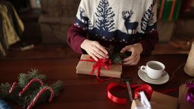 Dichte mening van man handen die een boog op binden giften voor Kerstmisvakantie dichtbij open haard Mannetje die huidige dozen b stock video