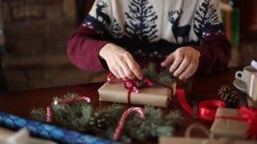 Dichte mening van man handen die een boog op binden giften voor Kerstmisvakantie dichtbij open haard Mannetje die huidige dozen b stock footage