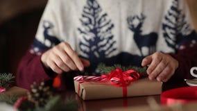 Dichte mening van man handen die een boog op giften voor Kerstmis binden dichtbij open haard, verpakkende dozen, die met spar ver stock video