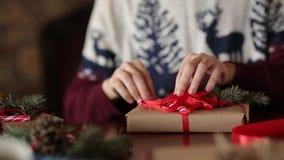 Dichte mening van man handen die een boog op giften voor Kerstmis binden dichtbij open haard, verpakkende dozen, die met spar ver stock footage