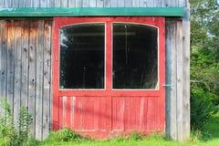 Dichte mening van rode staldeuren op een doorstaan houten gebouw met grote vensters en groen deurspoor stock afbeelding