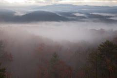 Dichte ochtendmist over rokerige bergen stock afbeeldingen