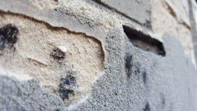 Dichte omhooggaand van as op een muur met een gat Stock Afbeelding