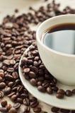 Dichte omhooggaand van de koffie omringd door koffiebonen Royalty-vrije Stock Fotografie