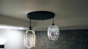 Dichte omhooggaand van de kroonluchter De ronde en vierkante lamp glanst op plafond stock videobeelden