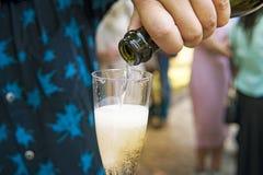 Dichte omhooggaand van een helft-gevulde die drinkbeker champagne door een mens bij de openlucht feestelijke gebeurtenis wordt ge stock afbeeldingen