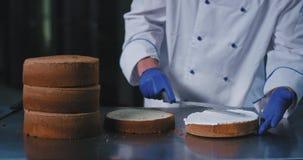 Dichte omhooggaand van een paar blauwe handschoenen die een spatel houden en elegant de room uitspreiden overal de cake zodat het stock footage