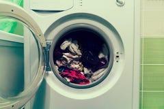 Dichte omhooggaand van een wasmachine laadde met kleren op witte achtergrond stock foto's